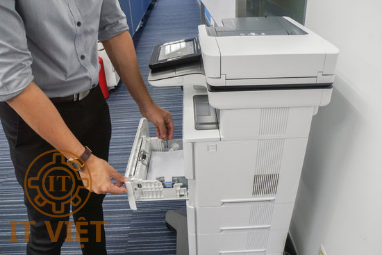 Businessman pull multi function office printer tray to put paper for printing documents